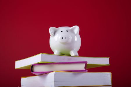 piggy bank over a stack of colorful books with a red background photo