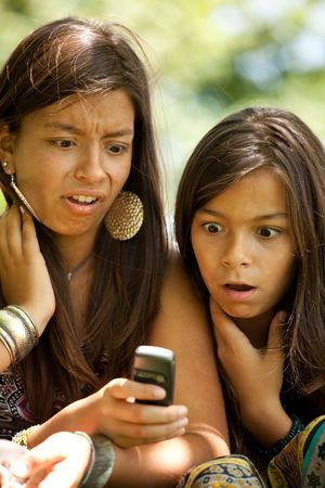 two young sisters reading a new sms at the cellular photo