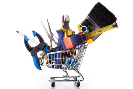 materials: mix of construction tools inside a shopping cart (isolated on white) Stock Photo