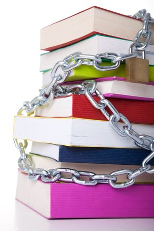 stack of colorful books protected with a chain (over a white background) photo
