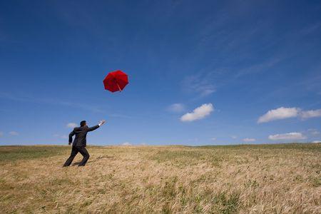 businessman chasing his insurance solution (an umbrella) photo