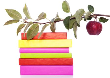 stack of colorful books and a branch with a fresh apple photo