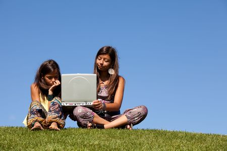 two young sisters using the internet at the park on her laptop photo