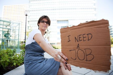resourceful: unemployed woman showing a message in a cardboard that she need a job Stock Photo
