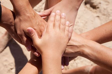 several: group of people stacking hands at the beach