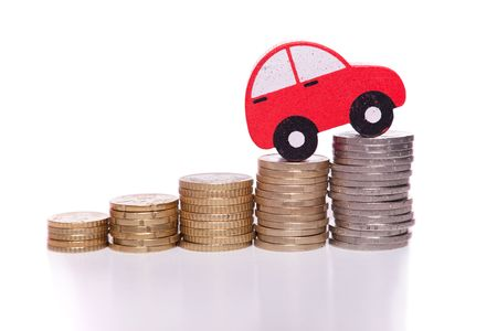 auto insurance: red car over a lot of stacked coins
