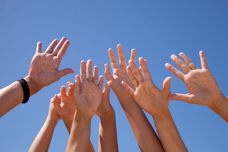 hands raised: many hands raised to the blue sky (some motion blur) Stock Photo