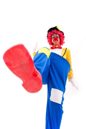 clown smashing something with his foot (isolated on white) photo