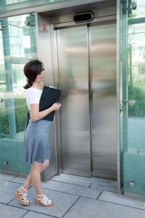 modern businesswoman waiting for the elevator photo