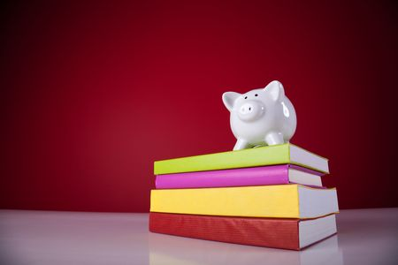 college fund savings: piggy bank over a stack of colorful books with a red background