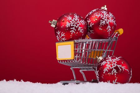 christmas balls in a shopping cart over a red background  photo