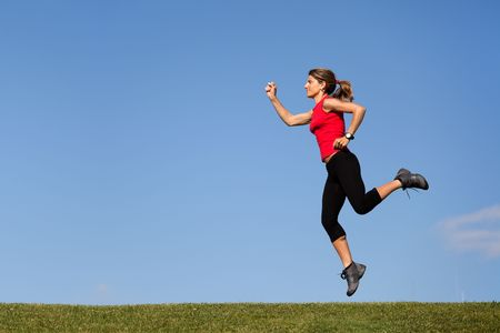 young woman jumping at the top of a hill photo