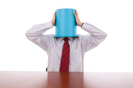 businessman trying to pull off the bucket on his head photo