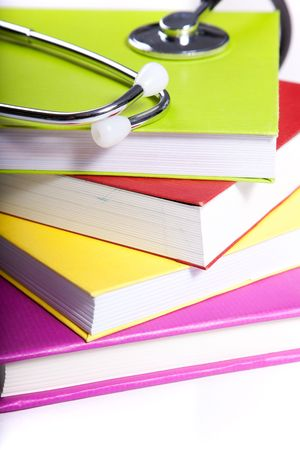 medical equipment and a stack of books isolated on white (selective focus) photo