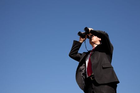 Businessman looking through binoculars with a blue sky as background  Stock Photo - 6317563