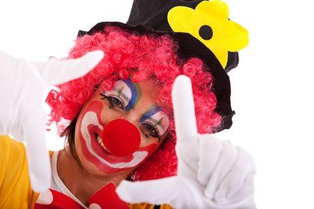 birthday clown: funny clown peeking between his fingers (hand framing) Stock Photo