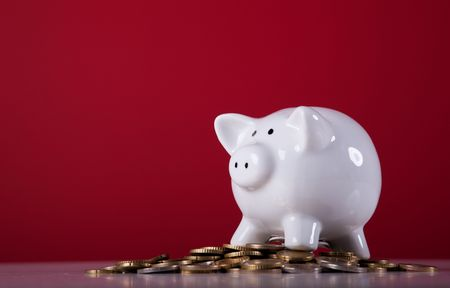 Piggy bank over a lot of coins with a red background photo