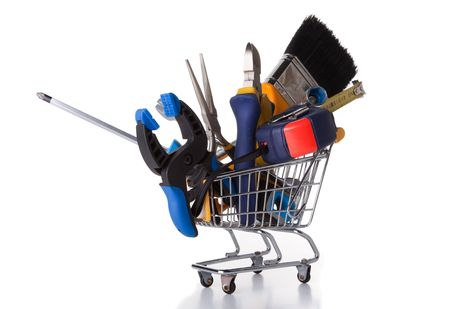 work material: mix of construction tools inside a shopping cart (isolated on white) Stock Photo
