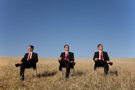 outdoor training: three businessman on the field, each one looking to one place Stock Photo