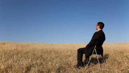 businessman sited in a chair looking to the landscape photo