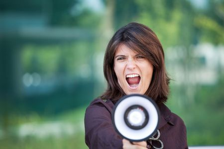 businesswoman shouting at the megaphone next to her office photo