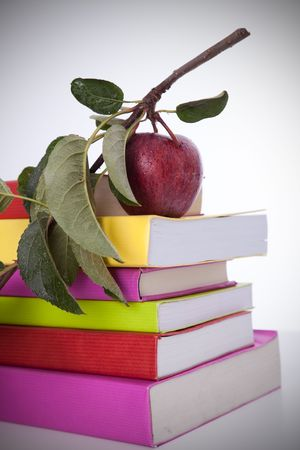 stack of colorful books and a branch with a fresh apple