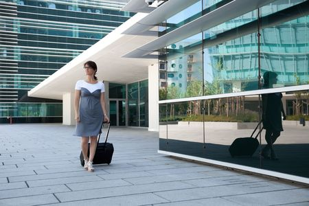 woman handle success: businesswoman walking with her luggage next to her office