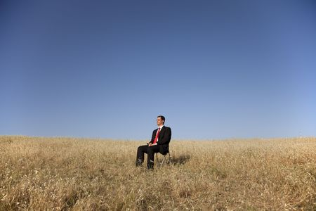 businessman in the field sited in a chair photo