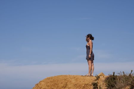 young woman looking at the view at a cliff photo