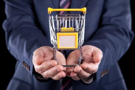 full shopping cart: businessman holding a shopping cart (selective focus)