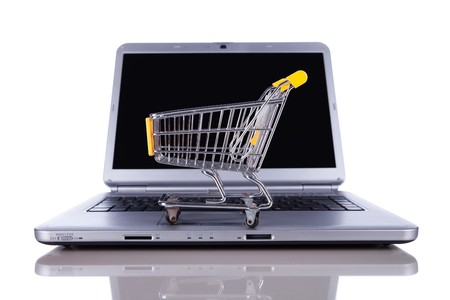 shoppingcart: shopping-cart over a laptop isolated on white with reflection