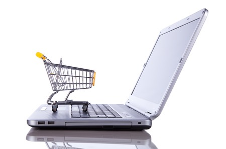 internet shopping: shopping-cart over a laptop isolated on white with reflection