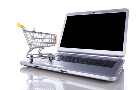 shopping-cart over a laptop isolated on white with reflection Stock Photo - 6954183