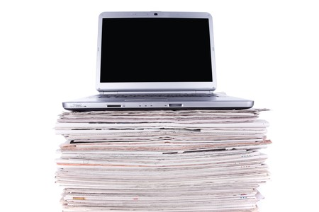 newspaper print: Laptop over a stack of newspapers for internet information access (isolated on white) Stock Photo