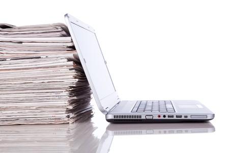 newspapers: stapel krant naast een laptop (geïsoleerd op wit)  Stockfoto