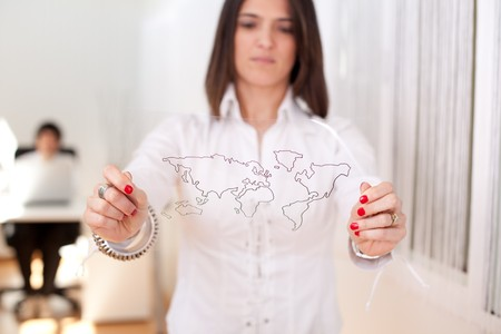 Happy businesswoman at her office showing a world map schema (selective focus with shallow DOF). Stock Photo - 6953838