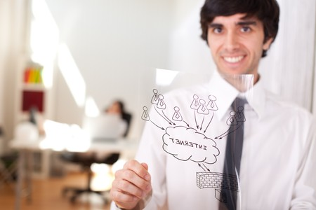 Happy businessman at his office showing a firewall schema (selective focus with shallow DOF). Stock Photo - 6953883