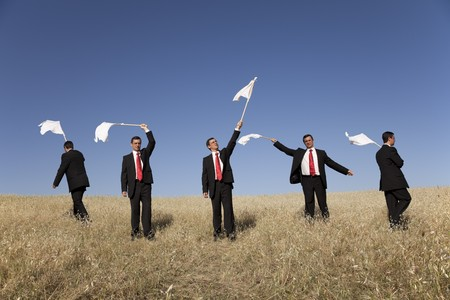 Group of businessman in the field raise the white flag photo