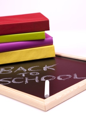 Back to school letters written on a blackboard with colorful books (selective focus) photo