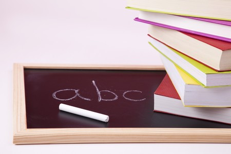 ABC letters written on a blackboard with colorful books (selective focus) photo