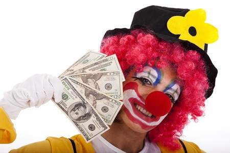 entertainment funny: funny clown showing some dollar bills (isolated on whites)