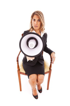 businesswoman seated on a chair speaking with a megaphone (isolated on white) photo