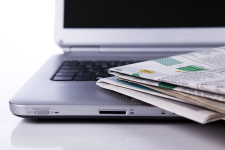 broadsheet newspaper: stack of newspaper over a laptop (selective focus) Stock Photo