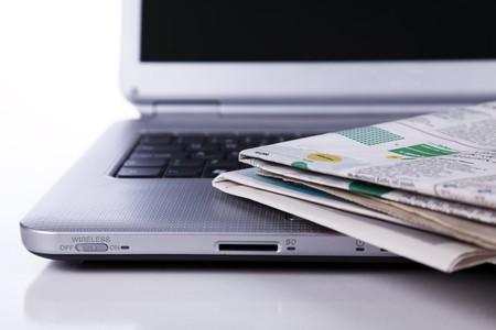 stapel krant over een laptop (selectieve aandacht)
