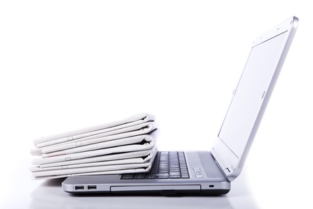 stack of newspaper over a laptop (selective focus) photo