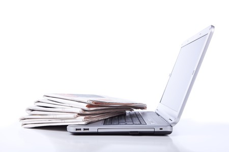publish: stack of newspaper over a laptop (selective focus) Stock Photo