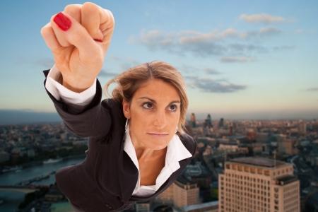 superwoman: Super businesswoman flying over London city