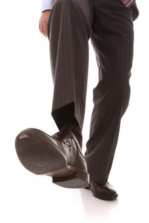 el zapato y la pierna de un paso de precaución de empresario (enfoque selectivo)
