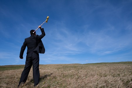 pollution free: businessman cleaning the field with a broom Stock Photo