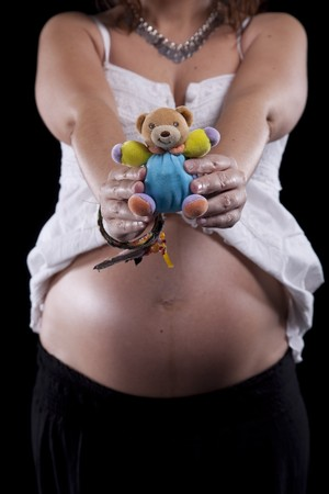 Pregnant woman showing the first toy for her baby photo